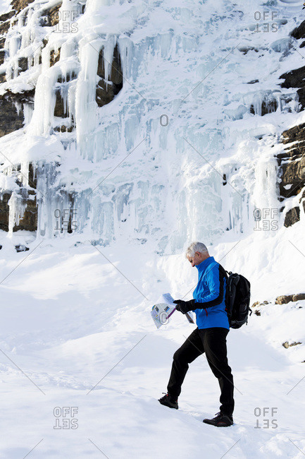 Male hiker on snow covered trail looking at map with a rock cliff covered in ice, Lake Louise, Alberta, Canada