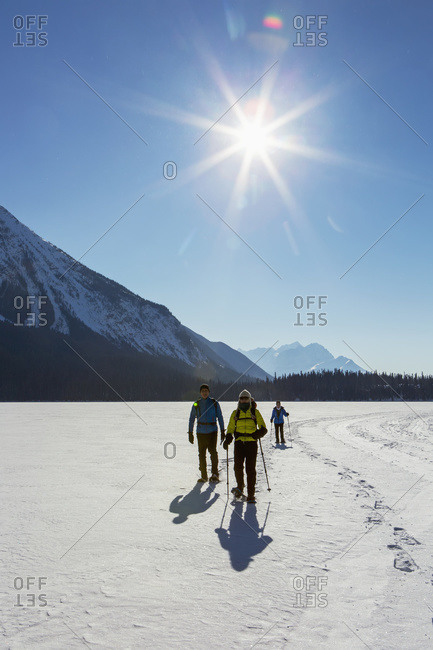 Group snowshoeing on snow covered mountain lake with sunburst and blue sky, Field, British Columbia, Canada