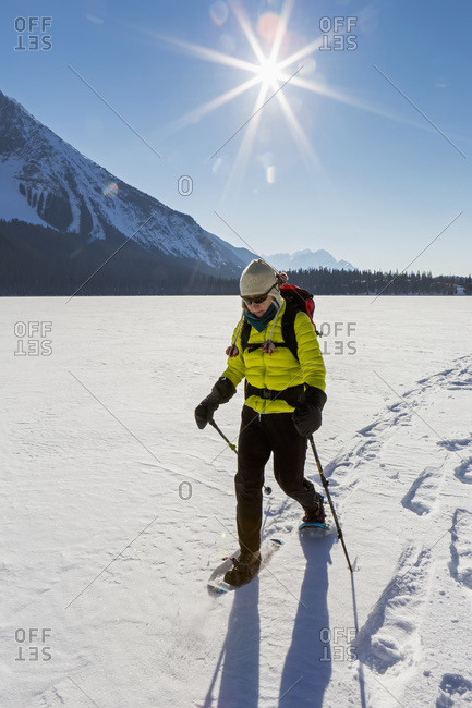 Female snowshoeing on snow covered mountain lake with sunburst and blue sky, Field, British Columbia, Canada