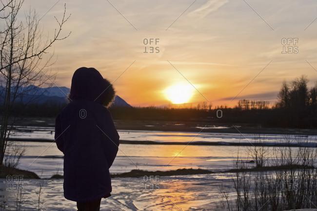 An Alaska native girl enjoying the sunset at Matanuska River in winter, Palmer, Alaska, United States of America