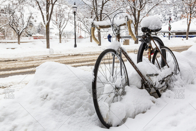 A road bike covered with snow sits by the side of a snowy road waiting for spring, Glenwood Springs, Colorado, United States of America