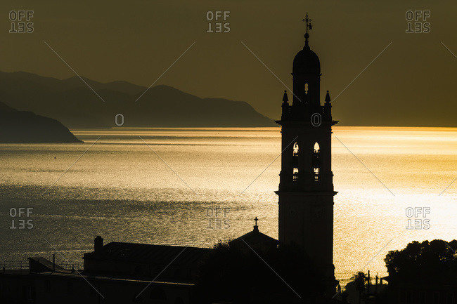 Golden sunlight reflected on water at dusk with tower of church, San Lorenzo della Costa, Liguria, Italy