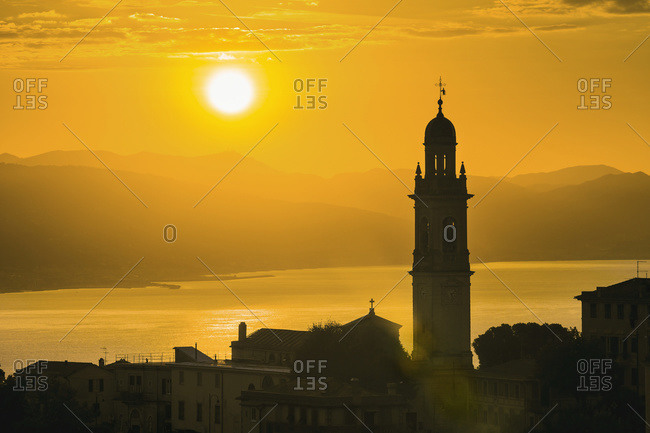 Golden sky at dusk with tower of church, San Lorenzo della Costa, Liguria, Italy