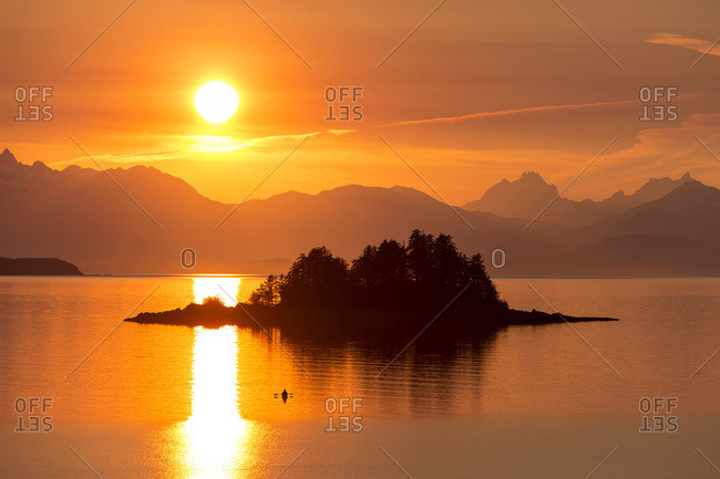 Sea kayaker at sunset, Favorite Channel, Inside Passage Alaska, near Juneau Chilkat Mountains and Lynn Canal beyond