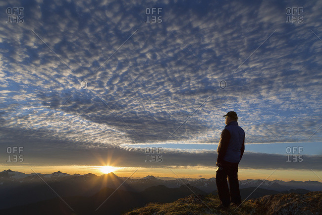 View of Coast Mountains and hiker at sunrise in the alpine on Douglas Island in Alaska's Tongass National Forest, Juneau Alaska