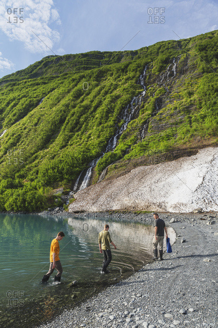 Man with two teenage boys on the beach in front of green mountain with waterfall at Shoup Bay State Marine Park, Prince William Sound, Valdez, Alaska, United States of America