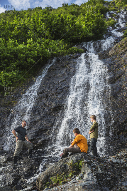 Man with two teenage boys on the rocks in front of a waterfall at Shoup Bay State Marine Park, Prince William Sound, Valdez, Alaska, United States of America