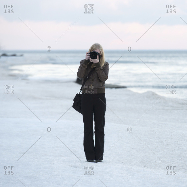 A woman stands on the beach with a camera pointed at the camera, Riverton, Manitoba, Canada