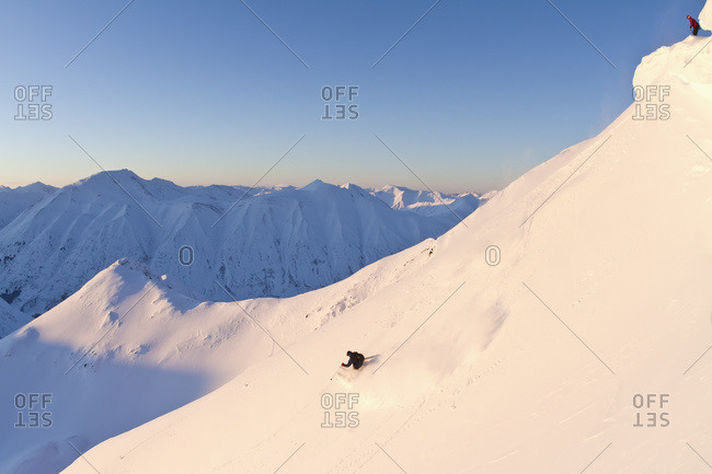 A skier watching another skier from above at Turnagain Pass, Kenai Mountains, South-central Alaska, Alaska, United States of America