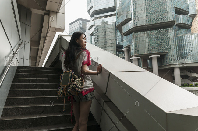 A young woman stands on steps looking out at buildings, Hong Kong, China