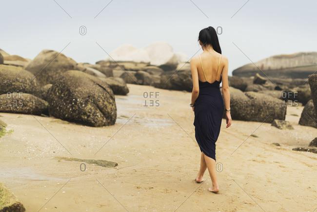 A model in formal dress walks barefoot on the sandy beach, Xiamen, China