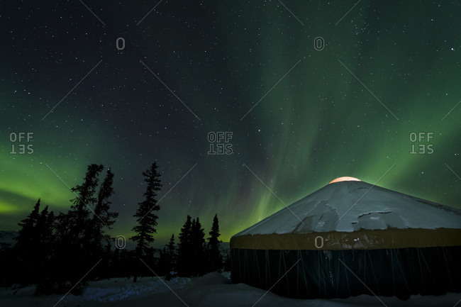 The bright neon green aurora illuminates above a yurt in the boreal forest, Chena River State Recreation Area, Fairbanks, Alaska, United States of America