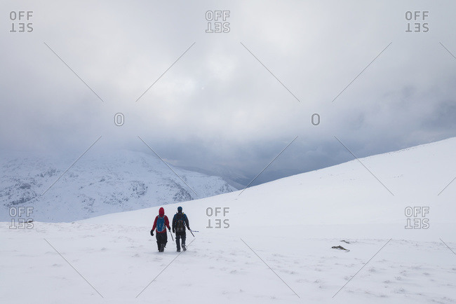 Two people walking in snow covered, winter conditions on Beinn an Dothaidh, near Bridge of Orchy, Argyll and Bute, Scotland