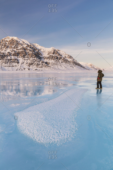 Man in a parka standing on overflow ice on the frozen Anaktuvuk River, Hoar frost crystals in the foreground, Napaktualuit Mountain in the background, Gates of the Arctic National Park, Alaska, United States of America