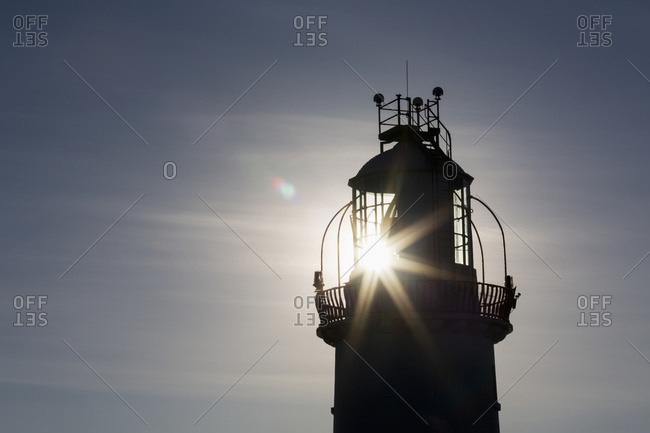 Silhouette of a lighthouse with a sunburst and blue sky, Kilkee, County Clare, Ireland