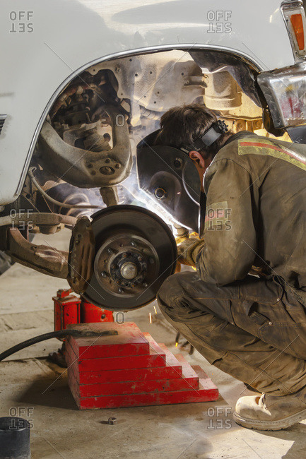 A welder wearing coveralls and his protective face shield is at work on a truck axle with a welding gun, Port McNeill, British Columbia, Canada