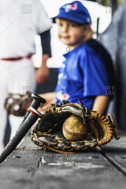 Ball players in uniform sit in the dugout with their glove and baseball in focus in the foreground, Fort McMurray, Alberta, Canada