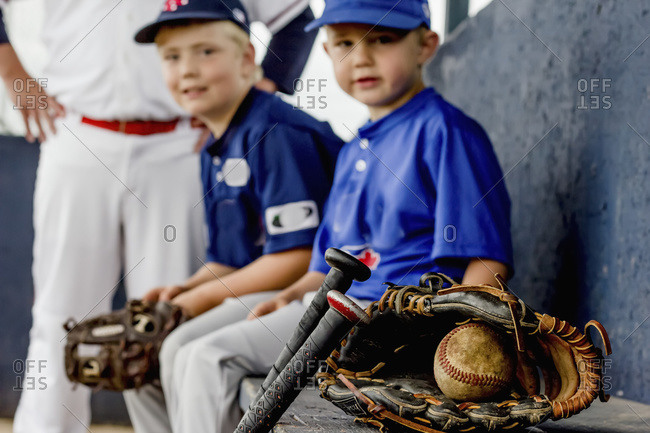 A closeup focus on a game used baseball and glove with young boy players in uniform sitting on the dugout bench in the background, Fort McMurray, Alberta, Canada