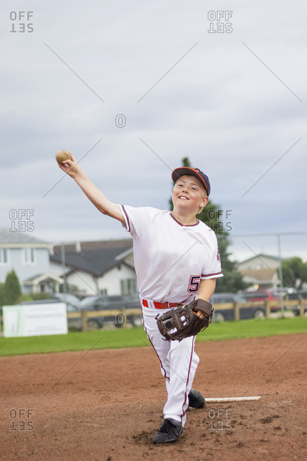 A young boy pitches the baseball from the pitchers mound during a ball game in a white uniform with a baseball and glove, Fort McMurray, Alberta, Canada