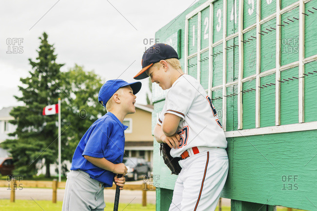 Two boys in baseball uniforms playfully argue in front of the scoreboard during a baseball game at a sports field, Fort McMurray, Alberta, Canada