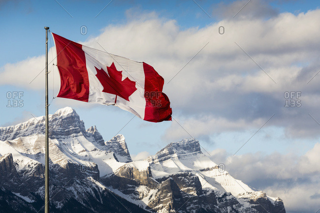 Canadian flag blowing in the wind on a flag pole with snow covered mountain range in the background with blue sky and clouds, Canmore, Alberta, Canada