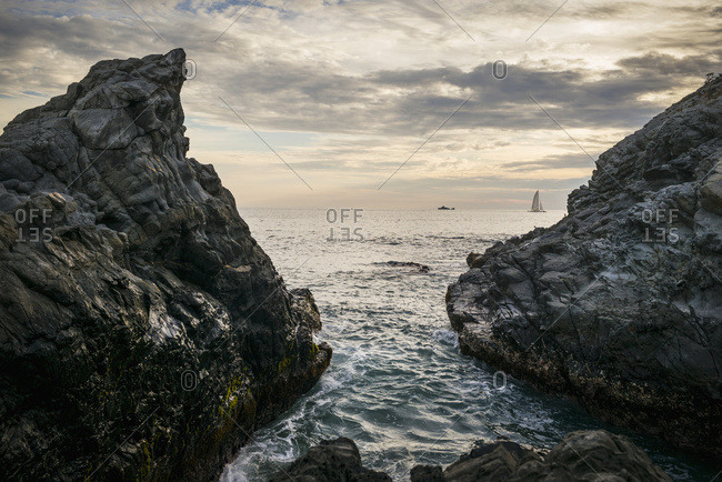 Rugged rocks on the coast with a view of ship and sailboat in the distance at sunset, Ixtapa-Zihuatanejo, Guerrero, Mexico