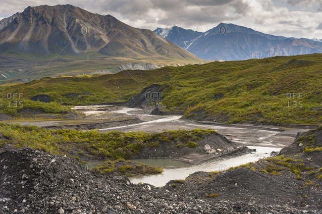 Thorofare River flowing next to the stone and vegetation covered Moldrow Glacier in Denali National Park and Preserve, Mount Eielson and the Alaska Range in the background, Alaska, United States of America