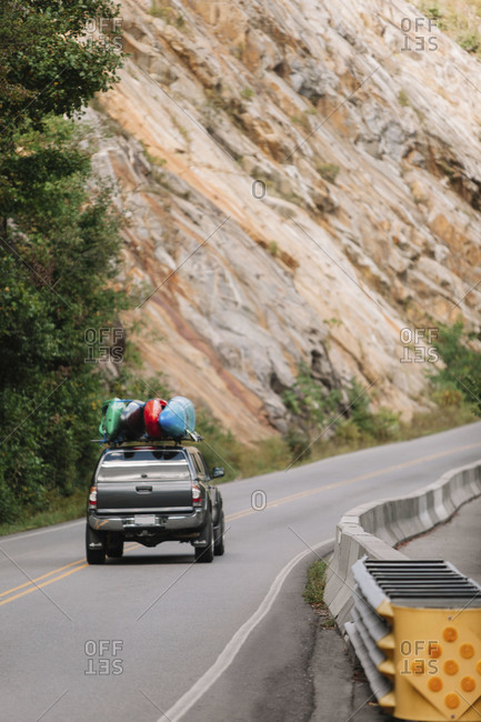 Truck with kayaks traveling on a mountain road