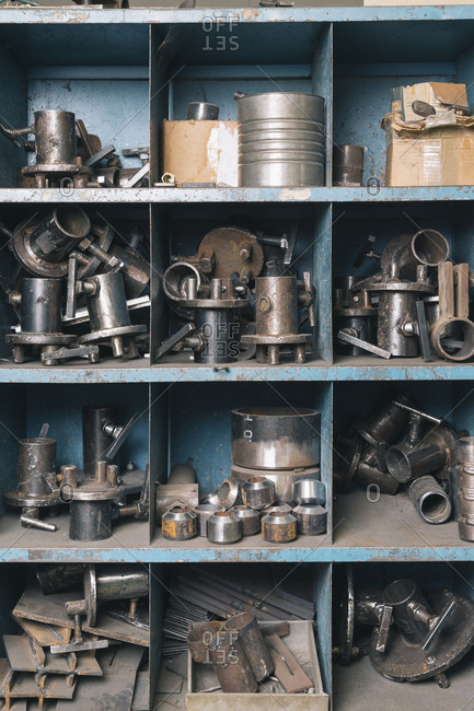 Grid of cubby holes  filled with metal parts of machinery