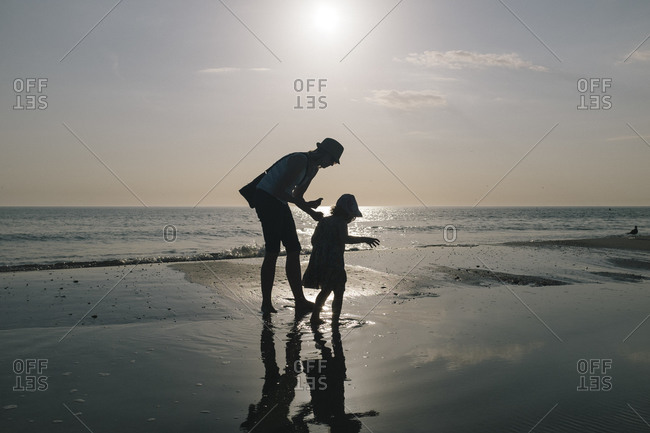 Mother and daughter looking for seashells on beach