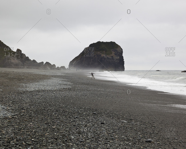 Person throwing stones into ocean from rocky beach