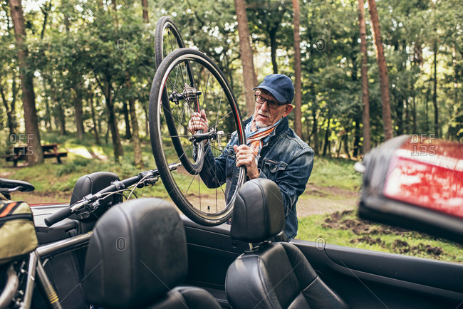 Senior man getting a bicycle from his car
