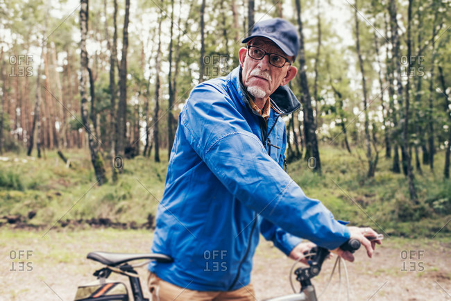 Senior man in a forest preparing for a bicycle ride