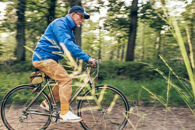 Senior man riding a bike on a trail in the woods