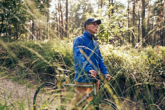 Senior man walking with a bicycle on a forest trail