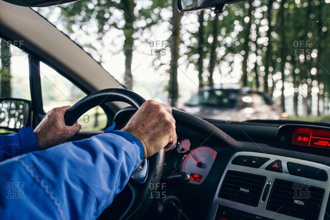 Hands of a senior man on a car steering wheel