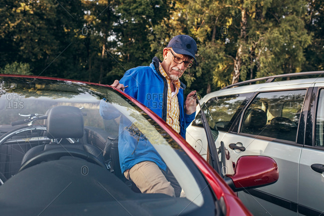 Senior man getting into his car