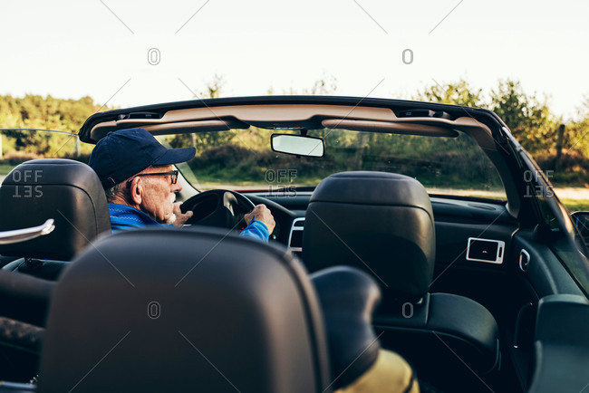 Rear view of a senior man sitting in his parked car