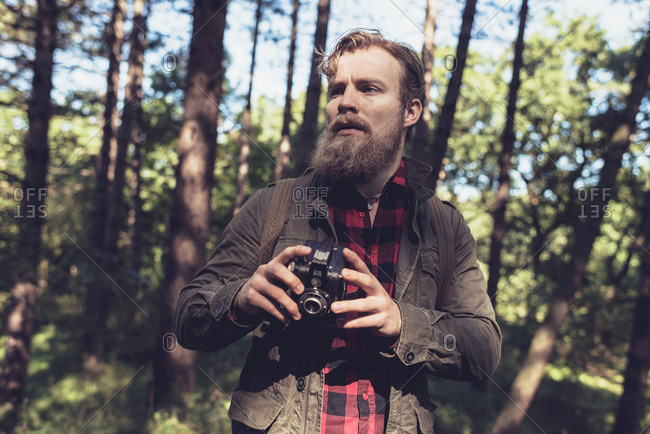 Hiker holding a vintage camera in the woods
