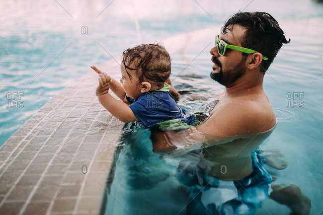 Father holding his son in a swimming pool