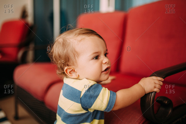 Toddler boy holding the arm of a patio sofa
