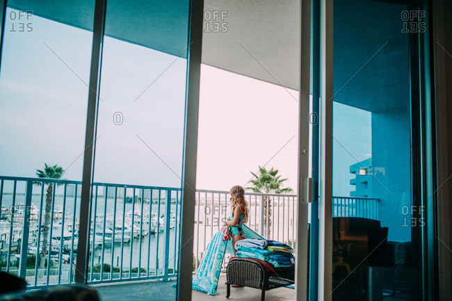 Little girl standing on a hotel balcony holding a pool float