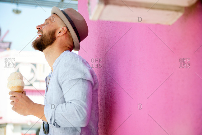 A man in a fedora laughs while eating ice cream