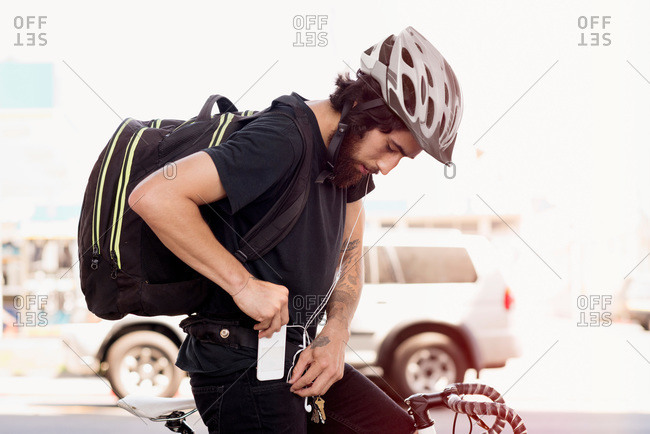 A cyclist puts his phone in his pocket
