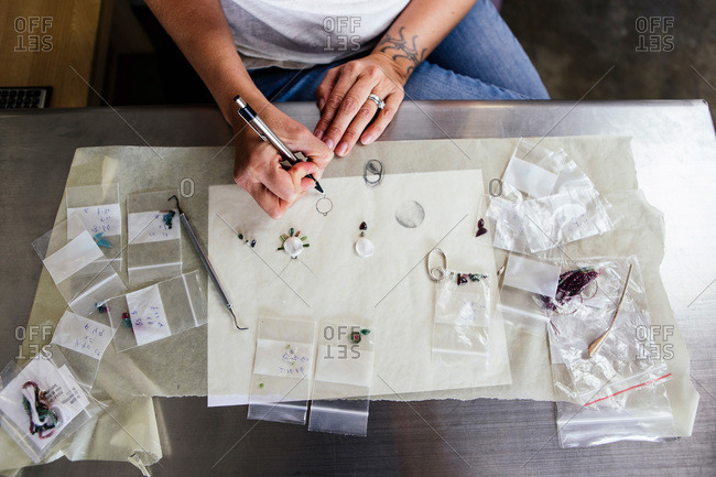 Woman sitting at a table designing jewelry
