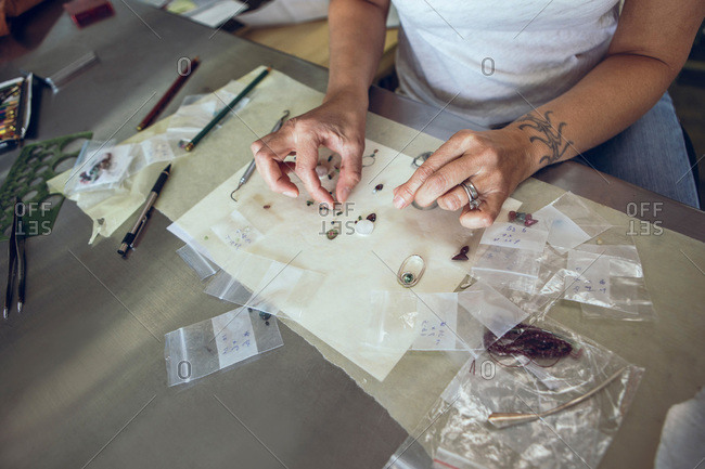 Woman designing beaded jewelry at a desk