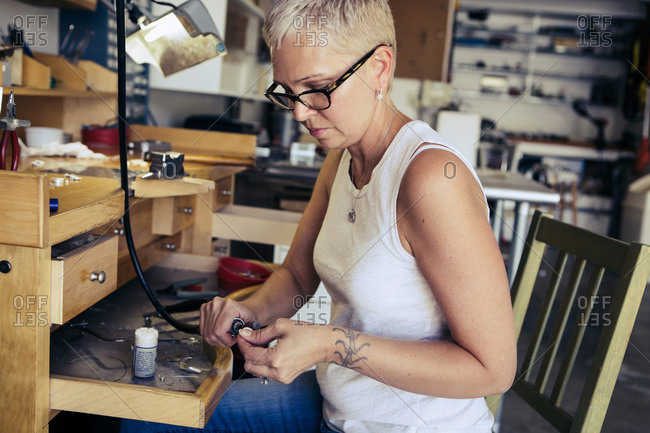 Woman filing the edge of a pendant in a jewelry studio
