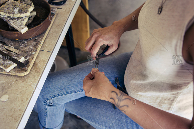 Woman using pliers to create a piece of jewelry
