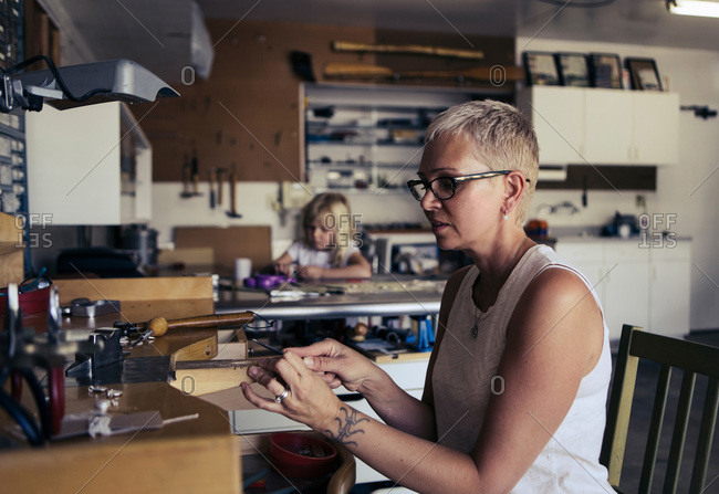 Woman filing a piece of jewelry in a studio