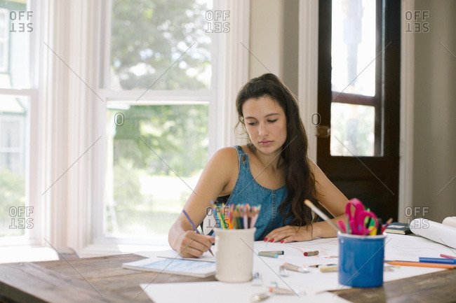 A young artist draws at her table